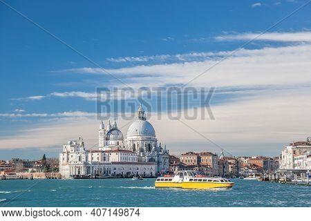 Grand Canal With Tourist Boat Against Basilica Santa Maria Della Salute In Venice, Italy