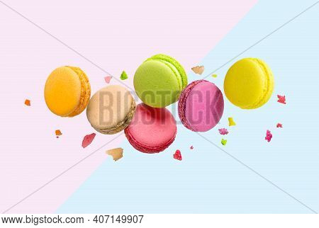 Traditional French Multicolored Macaroons Falling On Pink And Blue Background