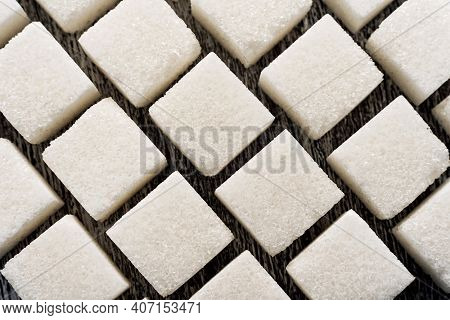 Sugar. Loose Sugar Lies In A Row On A Wooden Background. Lump Sugar In The Form Of Cubes