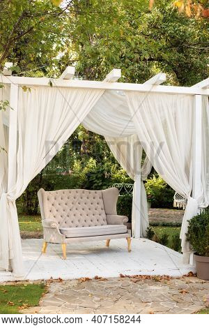Gazebo For Relax Outdoor. In Garden There Is Podium On Which Sofa In Style Of Provence Or Rustic. Su