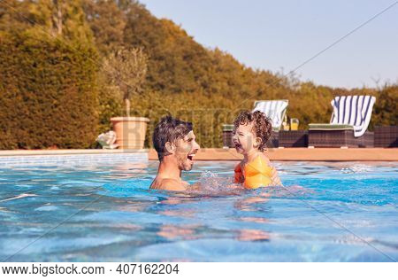 Father And Son In Outdoor Pool On Summer Vacation Teaching Son To Swim With Inflatable Armbands