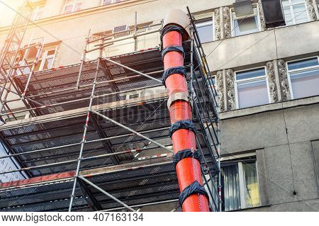 Scaffolding With Big Red Plastic Slide Chute For Rubble Debris Removal On Old Historica Building Fac