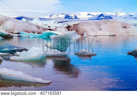 Cold July day. Bizarre icebergs and floating ice floes reflected in the smooth water of the lagoon. The lagoon Jokulsaurloun. Iceland. The concept of eco, northern and photo tourism
