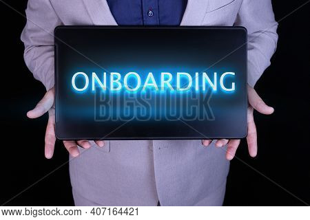 Onboarding Word, Text Written In Neon Letters On A Laptop Which Is Being Held By A Businessman In A