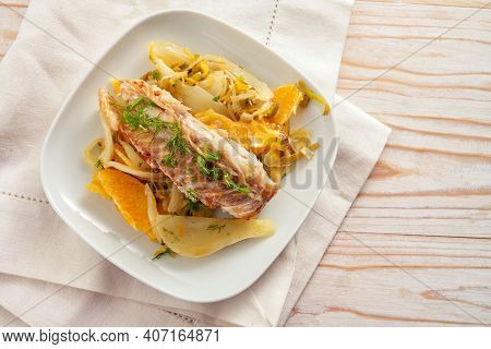Cod Fish Fillet On Fennel Vegetable With Orange Slices And Fennel Green Garnish On A White Plate And