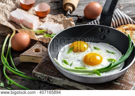 Portion Of Fried Eggs With Lard Bacon In Frying Pan With Pork Lard, Bread And Green Feathers Onions.