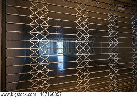 Closed Protective Rolling Shutter Grid From Metal In Front Of An Empty Shop In A Shopping Center, Ec