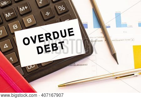 Text Overdue Debt On White Card With Metal Pen, Calculator And Financial Charts. Business And Financ