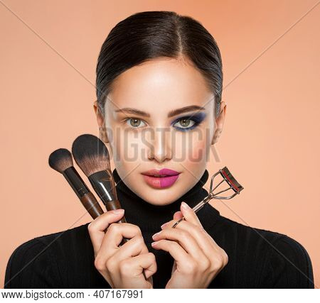 Portrait of a girl with  tools for making makeup near face.  One half face of a beautiful white woman with  bright makeup and the other is natural. Woman holds makeup brush and eyelash curler. Natural
