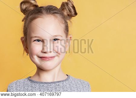 Close Up Portrait Of A Caucasian Girl With A Satisfied Expression Who Stands On A Yellow Background