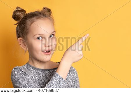 Close Up Of A Pensive Little Girl Looking At You And Pointing Her Finger At An Empty Space For Text.