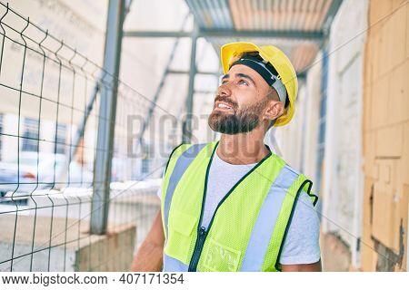 Young hispanic workman smiling happy walking at street of city
