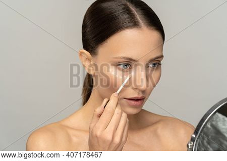 Woman With Natural Makeup Applying Concealer On Flawless Fresh Skin, Doing Make Up, Looking At Mirro