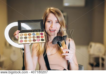Blonde Make-up Artist Shows Brushes And Palette Of Eyeshadow. Beautiful Woman Smiles And Holds Brush