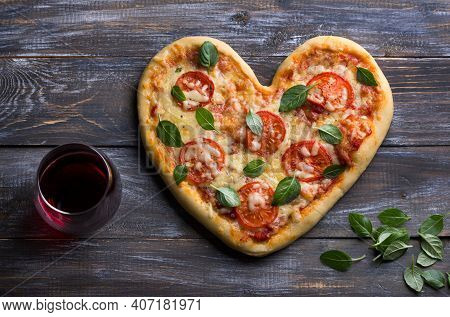 Homemade Delicious Margarita Pizza With Tomatoes And Basil In The Shape Of A Heart With A Glass Of R