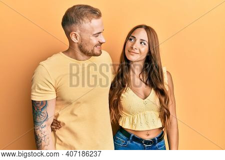 Young couple of girlfriend and boyfriend hugging and standing together smiling looking to the side and staring away thinking.