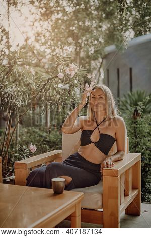Seductive Blond In Black Summer Clothing Relaxes On Her Holidays In Thailand. Young Woman Poses Sitt