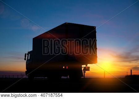 Truck Driver Transports Cargo On A Truck Against The Backdrop Of Sunset At Night. The Concept Of Com