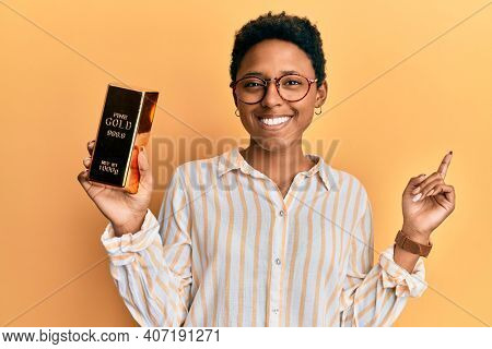 Young african american girl holding gold ingot smiling happy pointing with hand and finger to the side