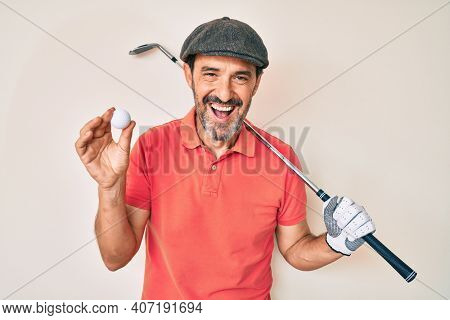 Middle age hispanic man holding golf club and ball smiling and laughing hard out loud because funny crazy joke.