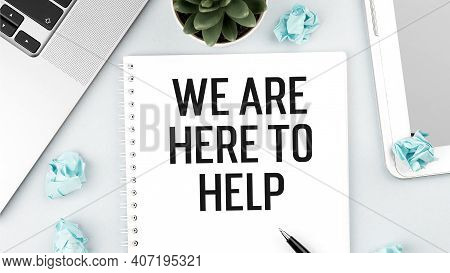 Word Text We Are Here To Help On Card With Laptop, Pieces Of Paper And Pen On Office Desk . Flat Lay