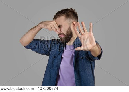 Terrible Smell Concept. Millennial Hipster Guy Closing His Nose And Gesturing Stop, Feeling Disguste