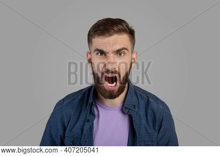 Portrait Of Young Bearded Guy Shouting Furiously, Expressing His Anger Over Grey Studio Background.