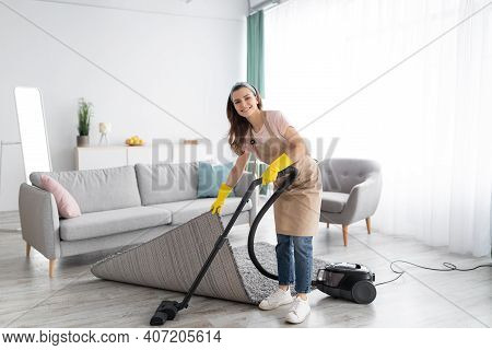 Positive Female Housekeeper Using Vacuum Cleaner To Tidy Modern Apartment. Happy Young Woman Doing D