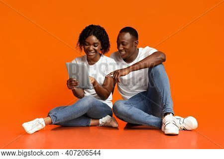 Smiling African American Lovers Sitting Together On Floor And Using Digital Tablet Over Orange Studi