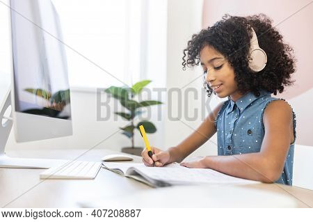 Cute Curly Schoolgirl In Headphones Is Enjoying Online Classes, Smiling Little Girl Fill In Workbook