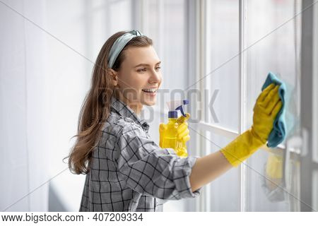 Portrait Of Young Pretty Lady In Rubber Gloves Cleaning Window With Detergent At Home. Lovely Millen