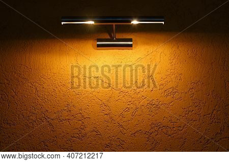 The Yellow Texture Wall Is Illuminated By A Light Fixture On Top. Background For Information Or Adve