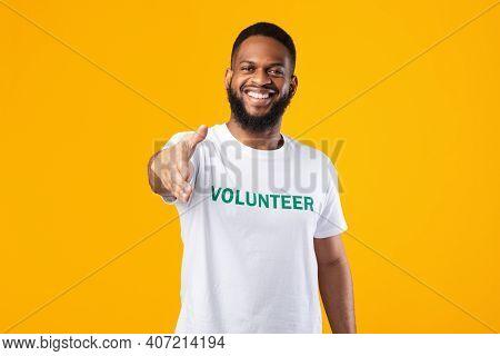 Cheerful Volunteer Guy Stretching Hand For Handshake Greeting To Camera Standing Posing In Studio Ov