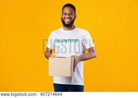 African American Volunteer Man Holding Donation Aid Box Standing On Yellow Studio Background, Smilin