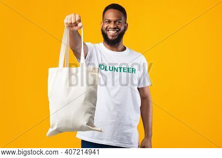 Stop Using Plastic. African Volunteer Man Showing White Eco Bag To Camera Posing Standing On Yellow