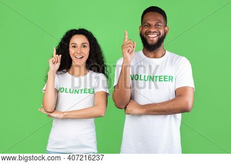 Two Multiracial Volunteers Having Idea Pointing Fingers Up Posing Standing Over Green Studio Backgro