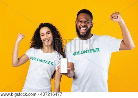 Volunteering. Two Diverse Volunteers Showing Smartphone With Blank Screen Recommending Volunteering