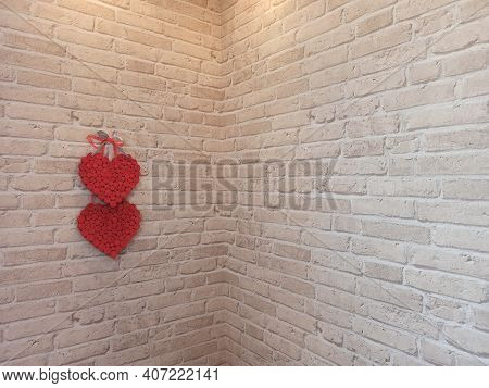 Red Hearts Hang On Brick Wall Near Corner Of Room. Textured Symbol Of Love. Two Handmade Hearts On W