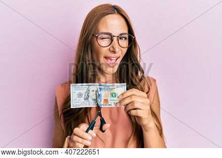 Young brunette woman cutting dollars with scissors for currency devaluation winking looking at the camera with sexy expression, cheerful and happy face.