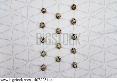 A Lot Of Quail Eggs On A White Tablecloth With Square Designs. Small Quail Eggs In Line