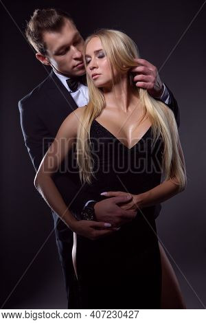 Elegant Couple In Love In A Passionate Embrace, Photo On A Dark Background
