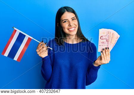 Young hispanic woman holding thailand flag and baht banknotes smiling with a happy and cool smile on face. showing teeth.