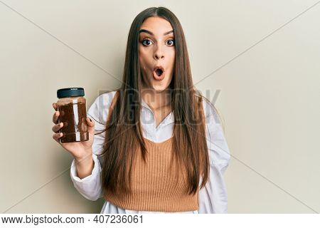 Beautiful brunette young woman holding soluble coffee scared and amazed with open mouth for surprise, disbelief face