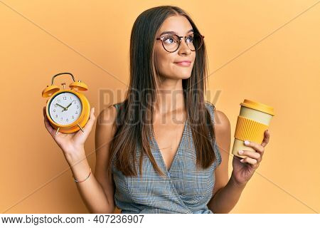 Young hispanic woman holding alarm clock and drinking a take away cup of coffee smiling looking to the side and staring away thinking.