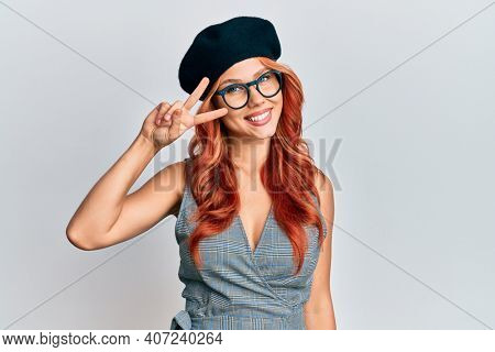 Young redhead woman wearing fashion french look with beret doing peace symbol with fingers over face, smiling cheerful showing victory