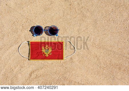 A Medical Mask In The Color Of The Montenegro Flag Lies On The Sandy Beach Next To The Glasses. The