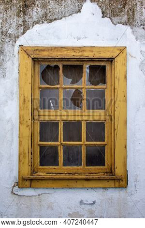 Vandalized Old Yellow Wooden Window With Broken Glass And Dirty Damaged White Walls. Detail Of Windo