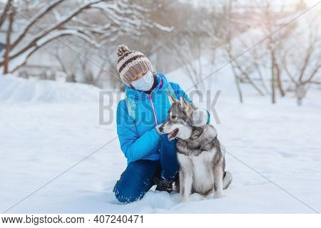 Alone Woman Using A Face Mask To Prevent The Spread Of The Coronavirus Walks With Her Dog In A Deser