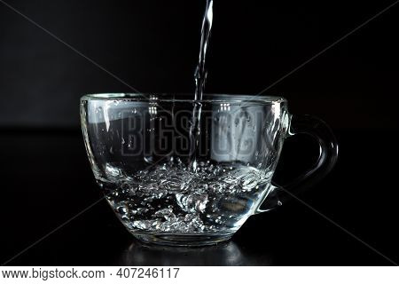 Pouring Water Into A Glass. Transparent Cup With Water On A Dark Background. Water Jet. Organic Wate