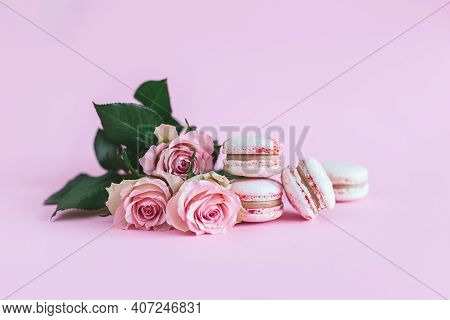 Tasty French Macaroons With Pink Roses On A Pink Pastel Background. Place For Text.